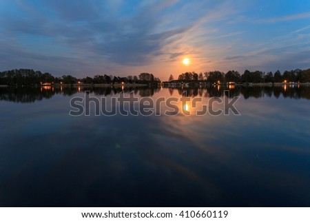 rural landscape at night with full moon and lake reflection