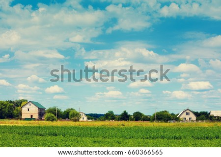 Rural landscape, field with blue sky and village