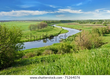 Rural landscape. Green field against the river and blue sky - stock photo