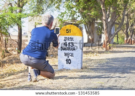 Rural landscape in Gujarat India on the route to Dwarka a holy city for Hindus and Mahabharata, Caucasian male taking a photo of the 413km milestone to Dwarka passing through Mahuva - stock photo