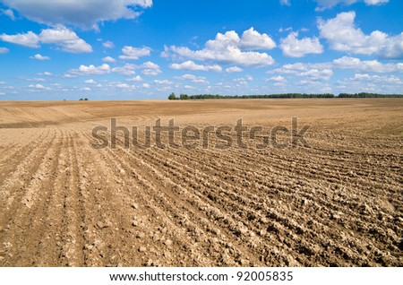 Rural landscape. Plowed field with a beautiful blue sky  and clouds.