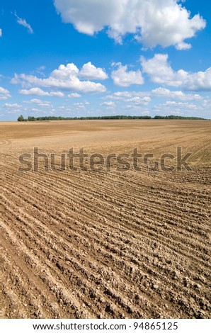 Rural landscape. Plowed field with a beautiful blue sky  and clouds. - stock photo