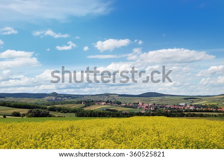 Rural landscape with a cozy village among the hills, fields and meadows under cloudy blue sky - stock photo