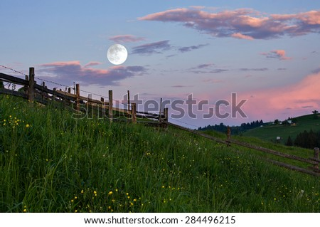 Rural landscape with a full moon at sunset - stock photo