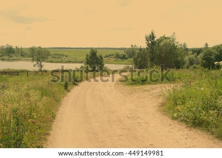 Rural landscape with a lane to the river going across the field (vintage style, subdued colors) - stock photo