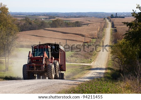 Rural landscape with a tractor pulling a trailer on foreground and hilly corn fields with a gravel road on background. - stock photo