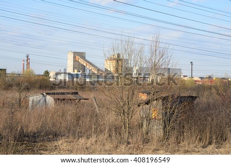Rural landscape with abandoned barn and the factory in the background on the outskirts of St. Petersburg, Russia. - stock photo