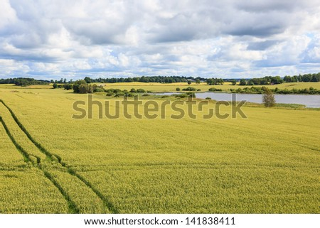Rural landscape with fields and a lake - stock photo