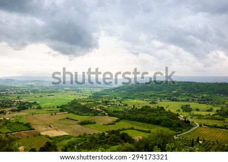 Rural landscape with fields, meadows, vineyards and farm houses in cloudy day. A view from the medieval town Gordes on the valley. Provence, France. - stock photo