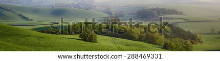 Rural  landscape with fields, waves and wooden hunting shack  - panoramic view - stock photo