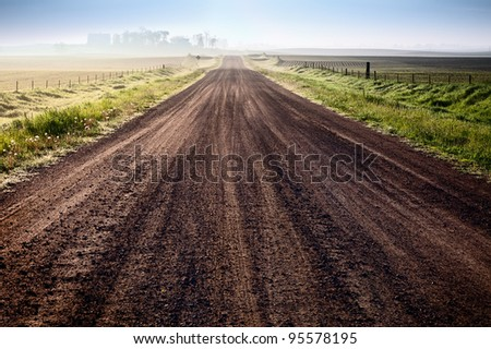 Rural landscape with gravel road and fields - stock photo