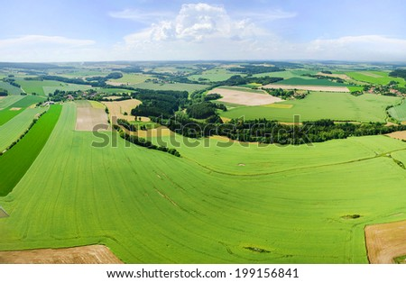 Rural landscape with green fields and rainy clouds - stock photo