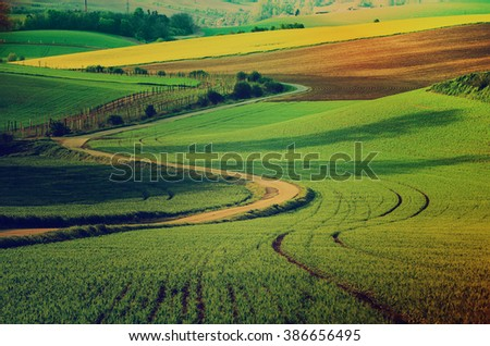 Rural landscape with green fields, road and waves, South Moravia, Czech Republic - natural seasonal retro hipster image - stock photo