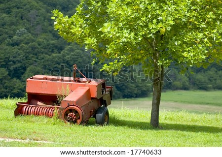 Rural landscape with lush green fields and broken tractor
