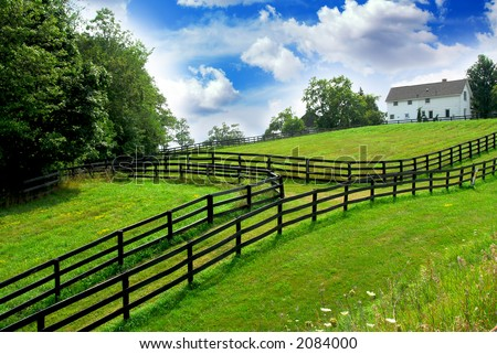 Rural landscape with lush green fields and farm house - stock photo