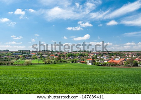 Rural landscape with lush green wheat with typical European village in the background - stock photo