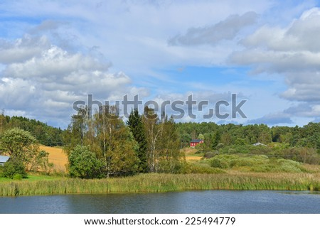 Rural landscape with river and red house in distance - stock photo