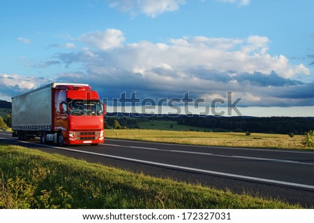 Rural landscape with road and moving red truck, cerulean sky with clouds