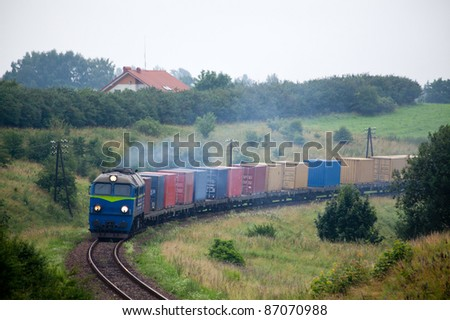 Rural landscape with the container train passing through countryside - stock photo