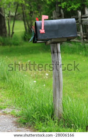 Rural mailbox on a old wooden post out on a country road. - stock photo