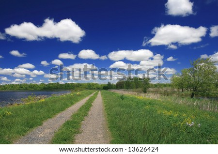 Rural (meadow, road, lake) landscape, cloudscape, rich blue colors (Montezuma Park in upstate New York in the Finger Lakes Region) - stock photo