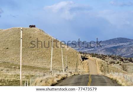 Rural Montana Scene with a Tractor on a Hill and a Paved Road that turns to dirt. - stock photo