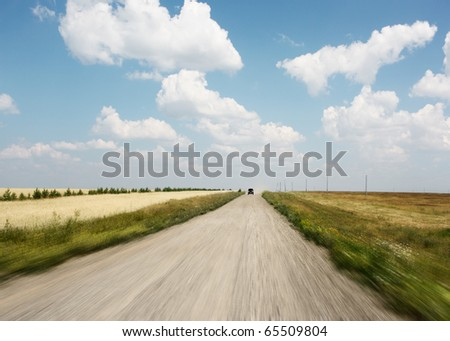Rural motion blurred road and blue sky with summer clouds