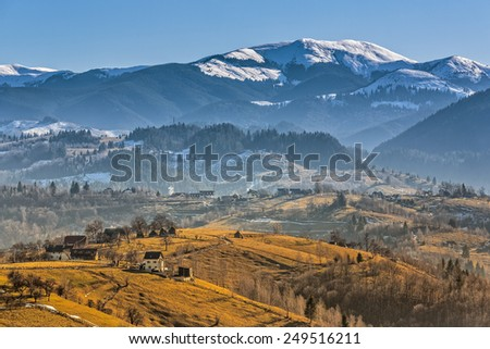 Rural mountain landscape with remote Romanian village uphill in the valleys of Bucegi mountains, Brasov county, Romania. - stock photo