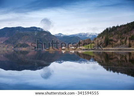 Rural Norwegian landscape with still lake water and mountains