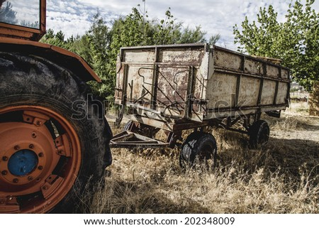 rural, old agricultural tractor abandoned in a farm field - stock photo