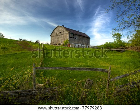 Rural Ontario farm scene of an old barn on a hill in spring time - stock photo