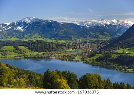 rural panorama landscape with lake Alpsee and alps mountains in Bavaria, Germany, nearby city Immenstadt - stock photo
