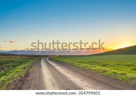 Rural path through meadow with green grass and mountains with snow peaks as background under clear sky on sunset in Iceland - stock photo