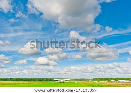 Rural plane on the runway in a field - stock photo