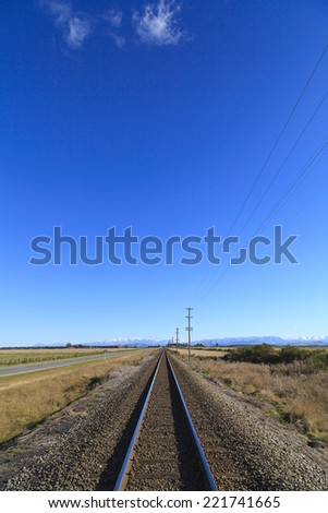 Rural railway straight to horizon under blue sky in Canterbury region, South Island, New Zealand. - stock photo