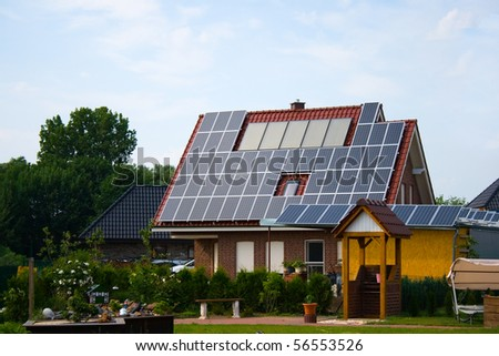 rural residence with solar panels on a roof - stock photo