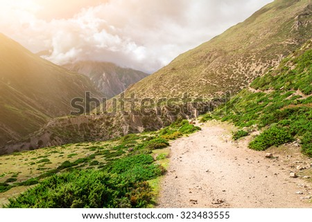 rural road and green plants in mountains with cloudy sky in Nepal, Annapurna trekking - stock photo