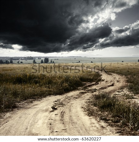 Rural road and storm clouds - stock photo