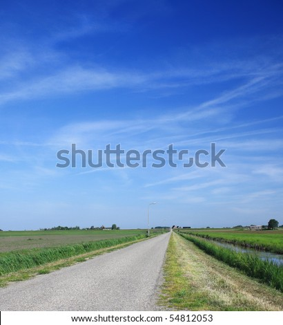 Rural road between fields leading to village