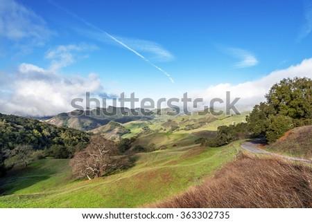 Rural road & coastal hills / mountains, blue sky, white clouds, & green meadows, on the Big Sur coast, California Central Coast, near Cambria CA. - stock photo