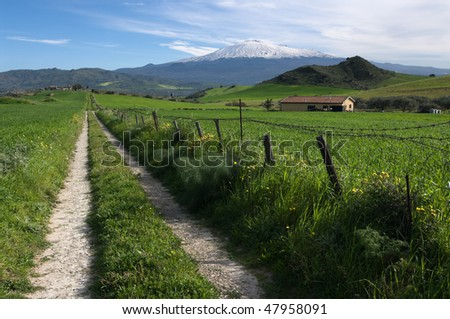 rural road crosses farmland to the slopes of mount Etna covered by snow - stock photo