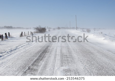 rural road in bad driving conditions. drifting blowing snow. - stock photo