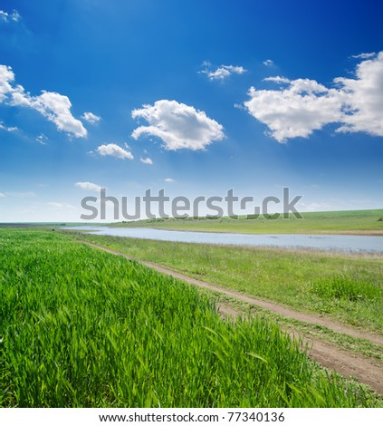 rural road in green grass and cloudy sky - stock photo