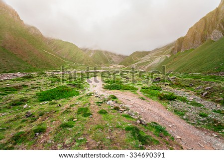 rural road in stone valley in mountains with green bushes and cloudy sky in Nepal, Annapurna trekking - stock photo