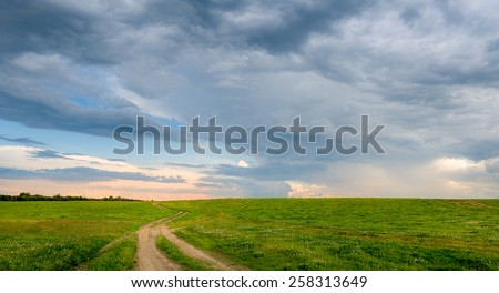 Rural road in the fields with dramatic sky before sunset landscape. Belarus. - stock photo