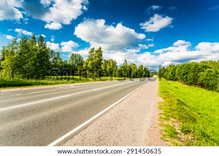 Rural road in the woods cloudy day - stock photo