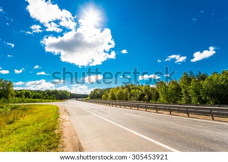 Rural road passing through fields and woods illuminated by the sun. View from the road - stock photo