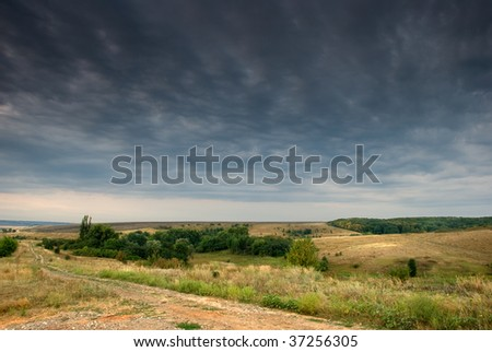 Rural road stretching out under grey clouds - stock photo
