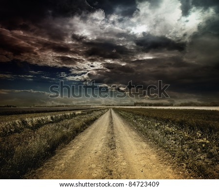 Rural road through a field at night - stock photo