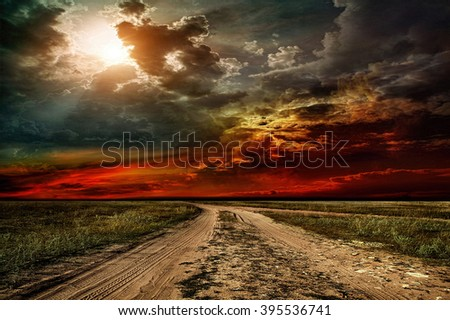 Rural road through the field before the storm - stock photo